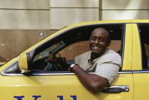 Cab driver leaning out of his yellow cab